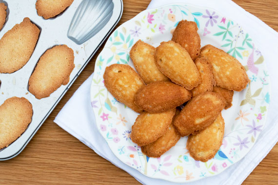 A plate of almond madeleines alongside a tray of warm madeleines