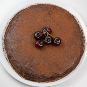 Cherry and chocolate cake on a serving plate