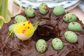 A chocolate cake decorated with eggs and a baby chick