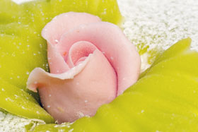 Two marzipan leaves and a rose inserted into a Swedish Princess Cake