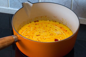 Milk and saffron threads being heated in a saucepan
