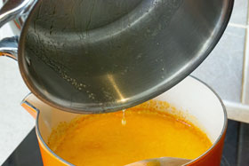 Melted butter being added to the saffron milk mixture