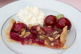 A portion of gooseberry and almond tart with whipped cream
