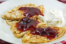 Pancakes with strawberry jam and whipped cream