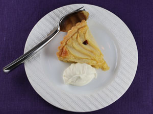 A slice of pear tart on a plate with lightly whipped cream