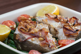Cod steaks cooked with beans and bacon