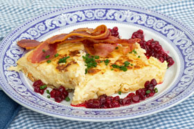 Wedges of Swedish egg cake on a plate with fried bacon and lingonberries