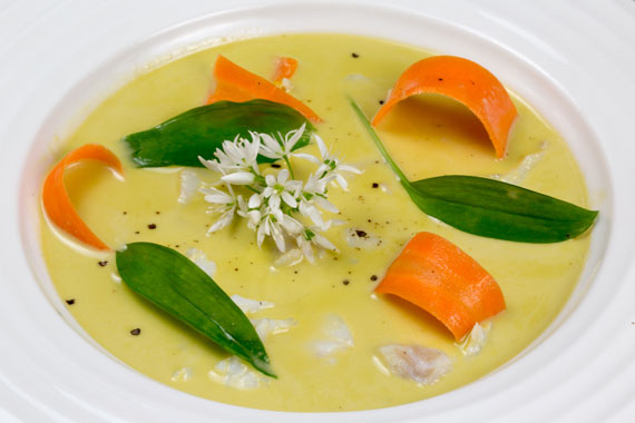 A dish of fish soup with wild garlic and carrots