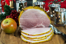 A boiled ham after it has been coated with mustard and breadcrumbs