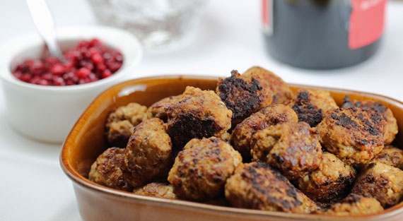 A dish of Swedish meatballs with lingonberry sauce in the background