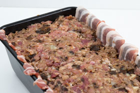 A loaf tin filled with minced meat for a country terrine