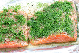 Two pieces of salmon covered with dill, ready to be cured